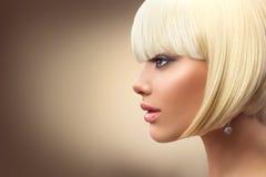 美好的有突然移动理发的时尚白肤金发的妇女 免版税图库摄影