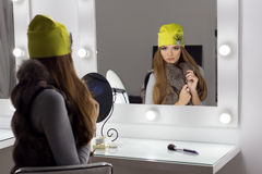 美好的有长的头发,时兴的盖帽的时尚性感的典雅的女孩在头坐明亮构成和绘的晚上 免版税库存图片