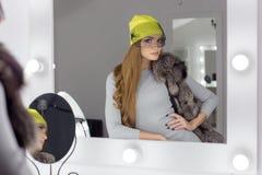 美好的有长的头发,时兴的盖帽的时尚性感的典雅的女孩在头坐明亮构成和绘的晚上 库存照片