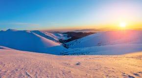 美好的桃红色日落亮光启迪与用雪和高山盖的公平的树的美丽如画的风景 免版税库存照片