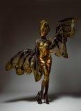美好的模型演播室画象与幻想金黄蝴蝶人体艺术的 免版税图库摄影