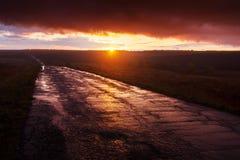 美好的横向本质 在雨以后的湿柏油路在日落 免版税库存图片