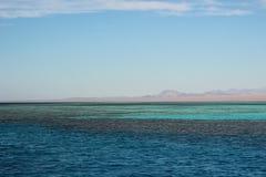 美好的横向 天蓝色的海运 埃及山和红海 在蓝天的轻的云彩 库存图片