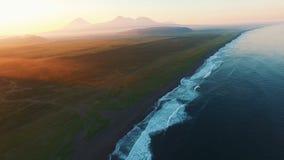 美好的横向 海和山在日落 飞行在沿海浪的直升机 股票录像