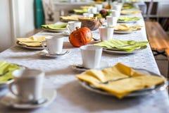 美好的欢乐饭桌五颜六色的黄色秋天helloween南瓜装饰咖啡杯茶碟板材和匙子 库存照片