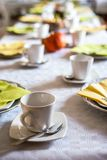 美好的欢乐饭桌五颜六色的黄色秋天helloween南瓜装饰咖啡杯茶碟板材和匙子 库存图片