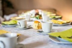 美好的欢乐饭桌五颜六色的黄色秋天helloween南瓜装饰咖啡杯茶碟板材和匙子 图库摄影
