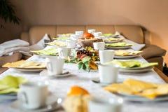 美好的欢乐饭桌五颜六色的黄色秋天helloween南瓜装饰咖啡杯茶碟板材和匙子 免版税库存照片