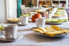 美好的欢乐饭桌五颜六色的黄色秋天helloween南瓜装饰咖啡杯茶碟板材和匙子 免版税库存图片