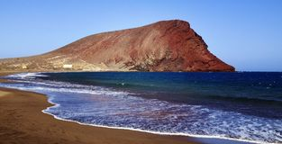 美好的沿海观点的Playa de与蒙大拿罗娅红色山的la Tejita La在El Medano,特内里费岛的Tejita海滩 免版税库存照片