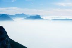 美好的法国阿尔卑斯冬天全景鸟瞰图风景有意想不到的兰色薄雾多云山背景 免版税库存照片
