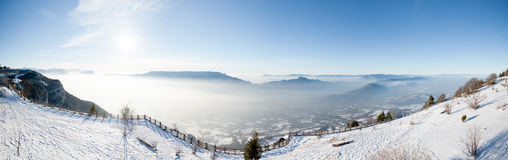 美好的法国阿尔卑斯冬天全景鸟瞰图风景有意想不到的兰色薄雾多云山背景 免版税库存图片