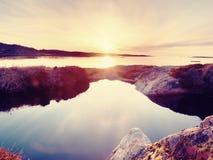 美好的海景 反映在水池的日落在岩石 光滑的海洋 库存照片
