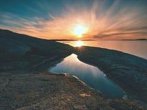 美好的海景 反映在水池的日落在岩石 光滑的海洋 库存图片
