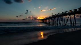 美好的海洋日出和轻拍在一老木渔码头延伸的波浪远旁边入海 严重的天空 免版税库存照片