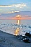 美好的海滩日出在岩石跳船的一个夏天早晨 免版税库存图片
