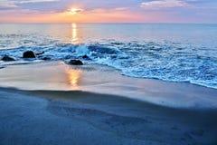 美好的海滩日出在岩石跳船的一个夏天早晨 免版税库存照片