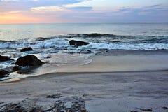 美好的海滩日出在岩石跳船的一个夏天早晨 库存照片