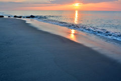 美好的海滩日出在岩石跳船的一个夏天早晨 图库摄影