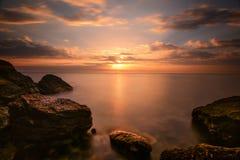 美好的海洋日出-风平浪静和冰砾向海岸线扔石头 免版税库存图片