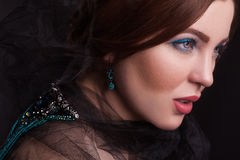 美好的深色的时装模特儿画象与黑面纱的和蓝色首饰和构成和在黑bakground的红色嘴唇 免版税库存照片