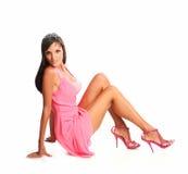 美好的深色头发的模型画象在siiting在地板上的桃红色礼服的 免版税库存图片
