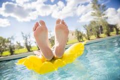 美好的漂浮在游泳池的脚和脚趾 库存照片