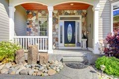 美好的灰色新的经典家庭入口外部与自然石头。 免版税库存照片