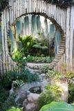 美好的热带亚洲样式有绿色与圈子竹墙壁装饰和小湖的庭院想法 库存图片