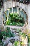 美好的热带亚洲样式有绿色与圈子竹墙壁装饰和小湖的庭院想法 免版税库存照片