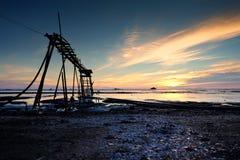美好的热带日落背景,在泥泞的海滩的木水泵塔 多云和黄色天空 图库摄影