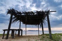 美好的热带海视图风景通过木村庄 叶状体顶房顶,沙滩和多云天空 库存照片