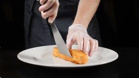 美好的烹调 餐馆食物烹调 把油煎的鳟鱼内圆角放的手套的厨师在白色板材上 慢的行动 HD 股票视频