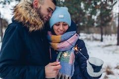 美好的爱恋的在冬天森林圣诞节和新年概念的夫妇灼烧的闪烁发光物 库存图片
