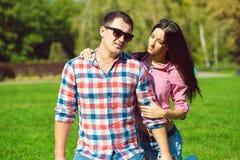年轻美好的爱恋的夫妇在控制中衬衣、牛仔裤和太阳镜坐绿色草坪 库存图片