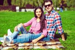 年轻美好的爱恋的夫妇在控制中衬衣、sittting在绿色草坪的牛仔裤和太阳镜 库存照片