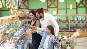 美好的父母和他们的女儿在超级市场选择甜点 股票录像