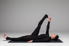 美好的瑜伽妇女实践瑜伽在灰色背景摆在 免版税库存图片