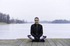 美好的瑞典白种人健身青少年的女孩坐木桥梁室外在冬天风景 免版税库存图片