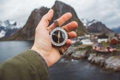 美好的男性手拿着一个磁性指南针以房子和山岩石为背景在海湾 免版税库存图片