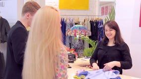 美好的白种人夫妇在商店选择衣裳并且去现金书桌 股票视频