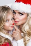 美好的白肤金发的女性模型,有女儿的母亲在圣诞老人服装穿戴了 免版税库存图片