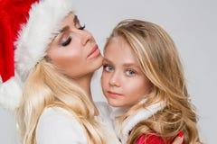 美好的白肤金发的女性模型,有女儿的母亲在圣诞老人服装穿戴了 免版税图库摄影