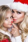 美好的白肤金发的女性模型,有女儿的母亲在圣诞老人服装穿戴了 库存照片