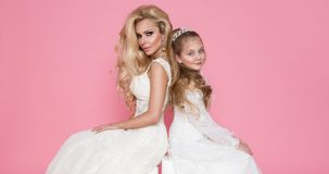 美好的白肤金发的女性模型,有白肤金发的女儿的母亲礼服的 图库摄影