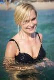 美好的白肤金发的妇女游泳在海洋 免版税库存图片