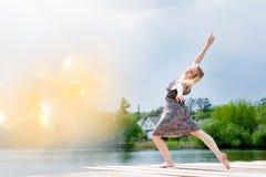 美好的白肤金发的小姐跳舞画象象天使的在水湖和太阳照明设备奇迹的轻的礼服飘动 免版税图库摄影