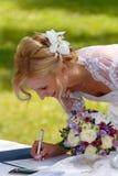 美好的白肤金发的微笑的新娘签的合同 库存图片