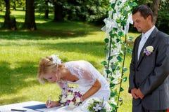 美好的白肤金发的微笑的新娘签的合同 免版税库存图片