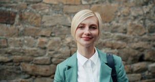 美好的白肤金发的微笑的看的照相机身分画象在砖墙附近的 影视素材